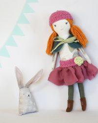 Lėlė dėvi nurengiamus drabužius: sijonas, kepurė, šalis, batukai.